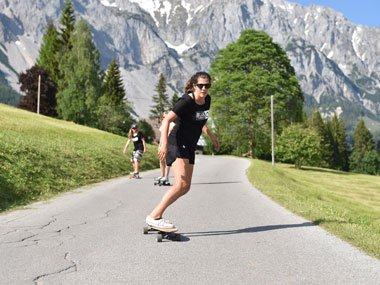 Longboard team rider on an Alpine road in Blue Tomato clothing