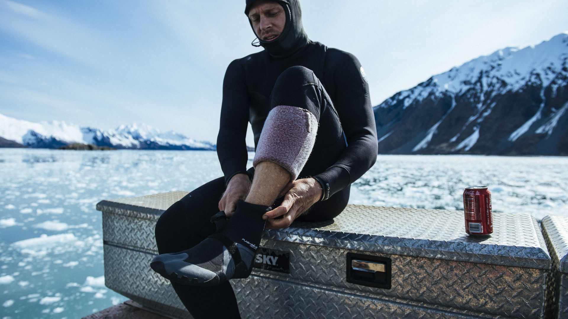 Professional surfer Mick Fanning putting on surf booties in Alaska