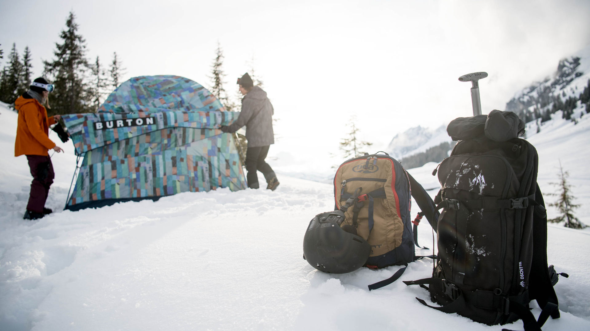 Two avalanche compatible rucksacks outside, with two riders and a tent