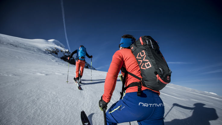 Skier hiking up the mountain with the Avabag avalanche backpack by Ortovox