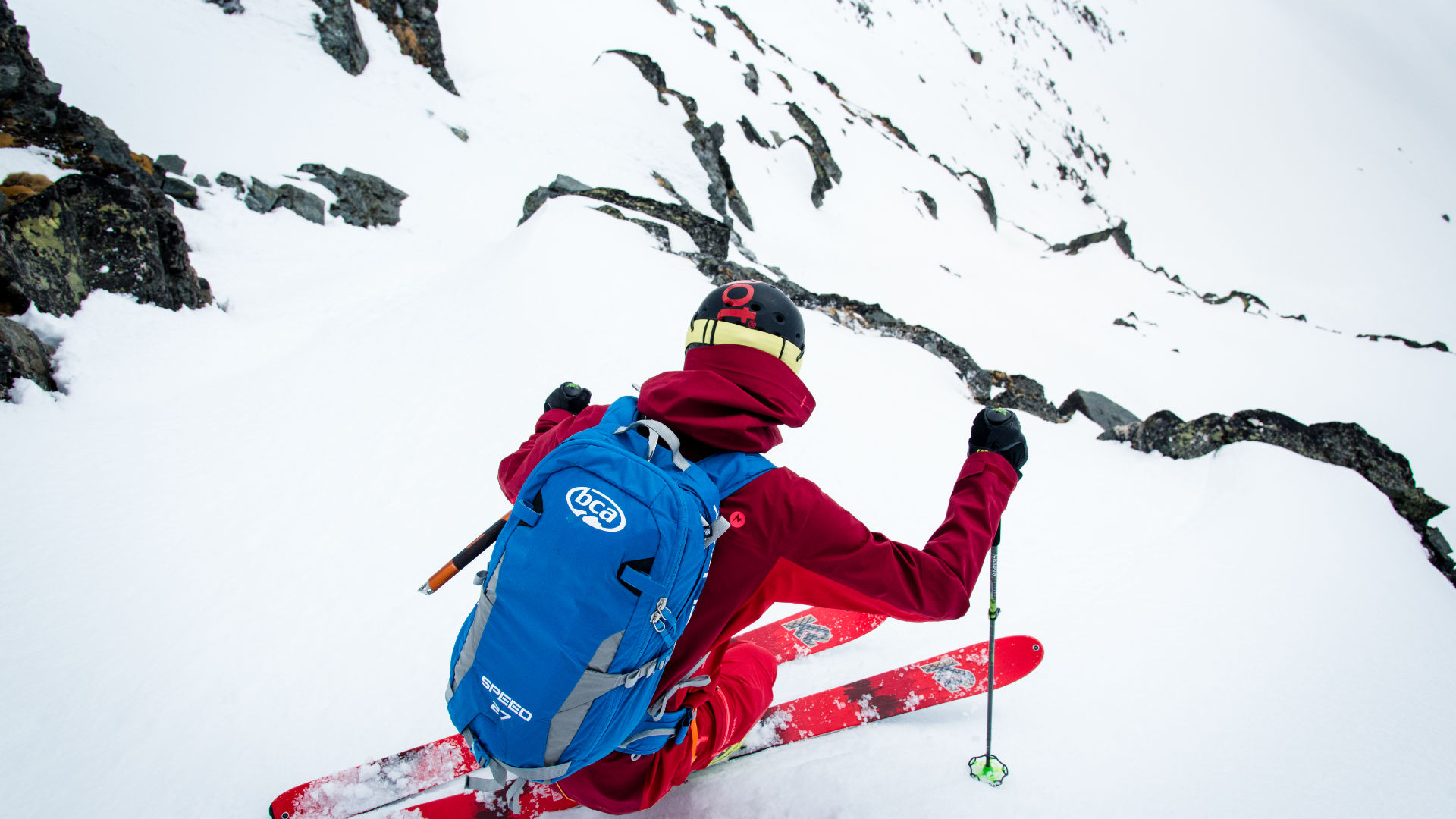 Freeride skier riding down a mountain with an avalanche backpack by BCA