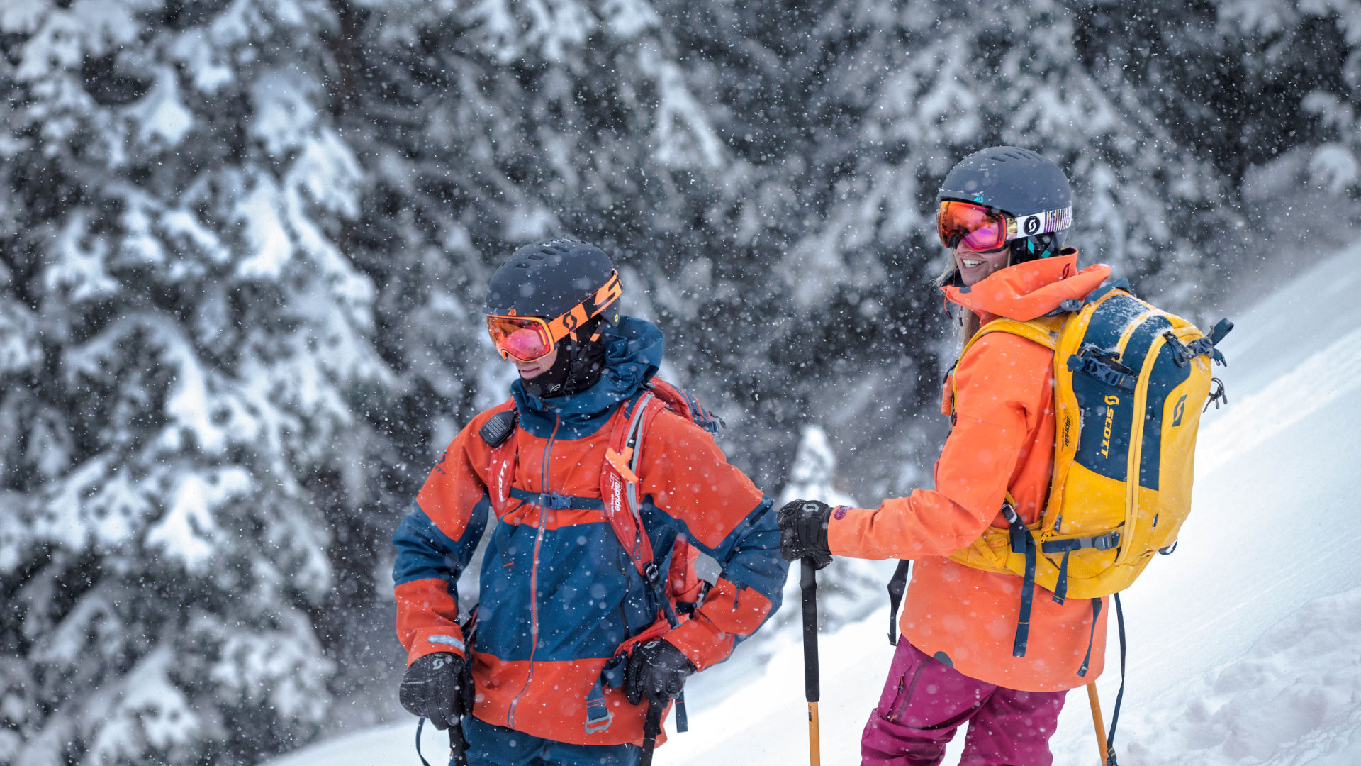Two freeride skiers standing in the snow, equipped with an avalanche backpacks looking for their run