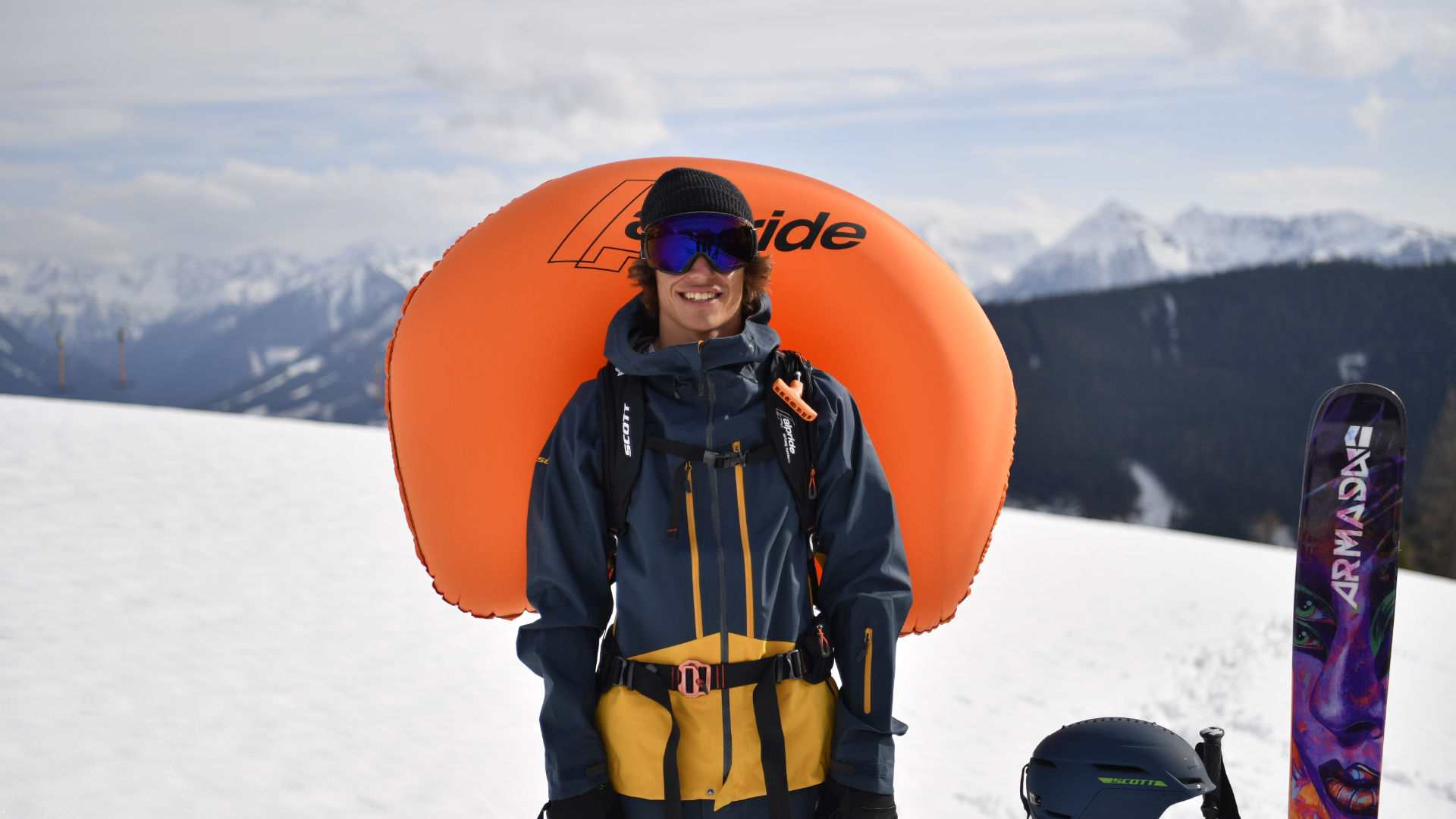 Freerider with an inflated Scott Alpride system standing outside next to his skis