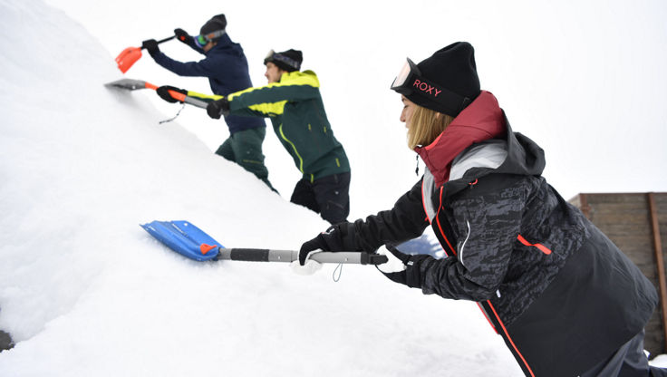 Snowboarders and skiers using their avalanche shovels to dig and build a jump