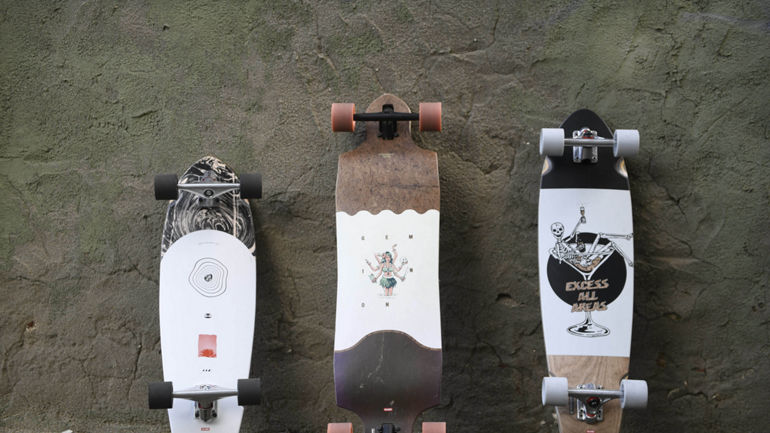 Different cruisers and longboards in front of a wall
