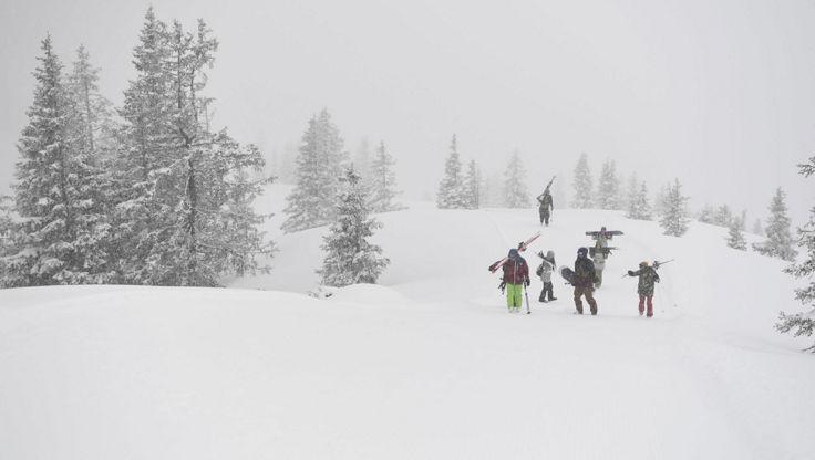 Skifahrer, die mit einer Antibeschlagbrille durch starken Schnee wandern.