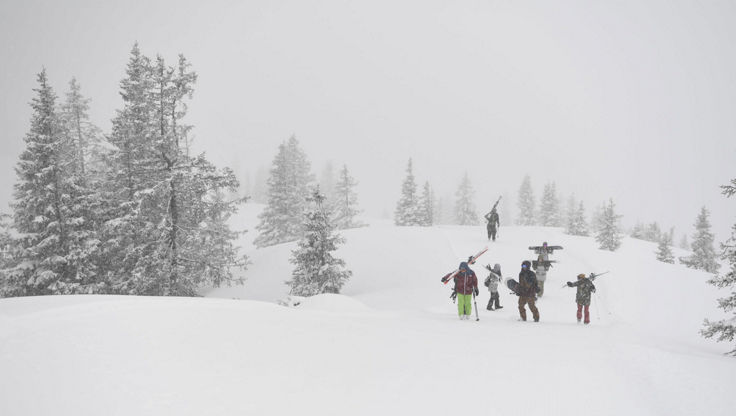 Skiers hiking through heavy snow with anti-fog goggles