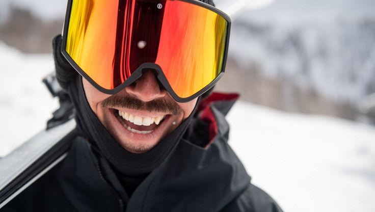 Ein Snowboarder mit einer großen Snowboardbrille in den Bergen.