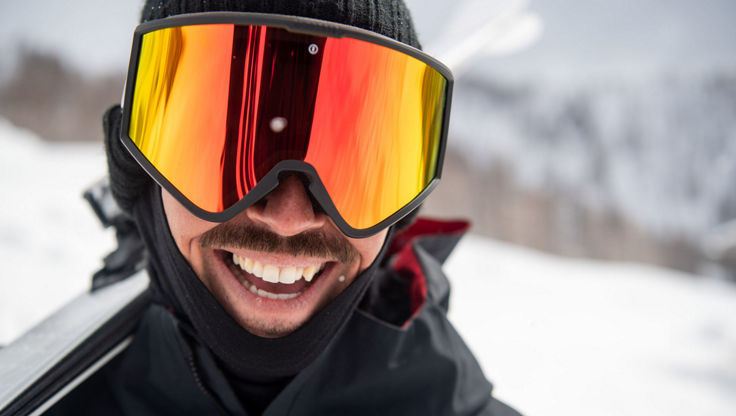 A male snowboarder wearing large snowboard goggles in the mountains