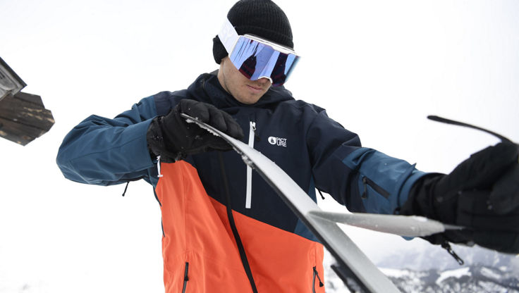 A male snowboarder wearing medium sized snowboard goggles from SPY Optics