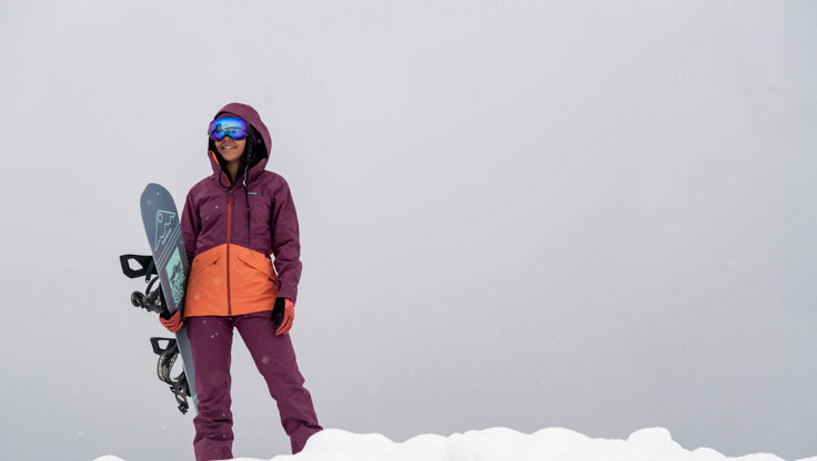 A female snowboarder in changeable conditions in the mountains