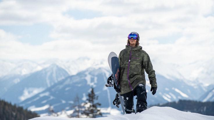 Snowboarder am Berg bei leicht sonnigem aber bewölktem Wetter