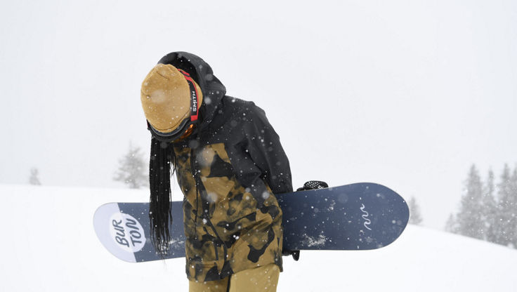 Snowboarderin in den Bergen bewölktem Himmel und Schneefall