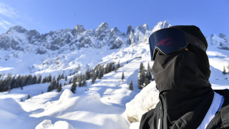 Male snowboarder outside fully coverd his face with bandana and goggle