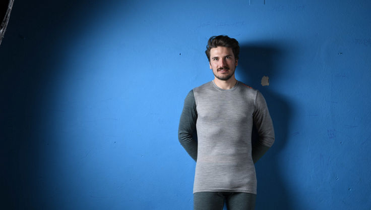 Man standing inside in front of an blue wall in merino wool base layers