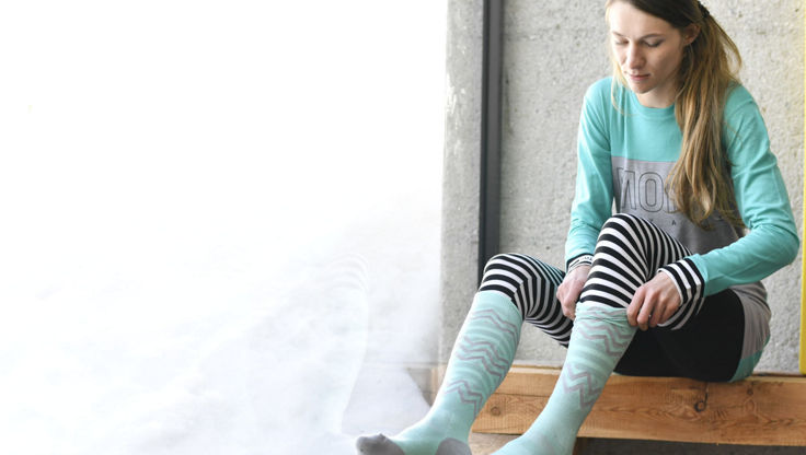 A girl in a base layer putting on a pair of technical socks