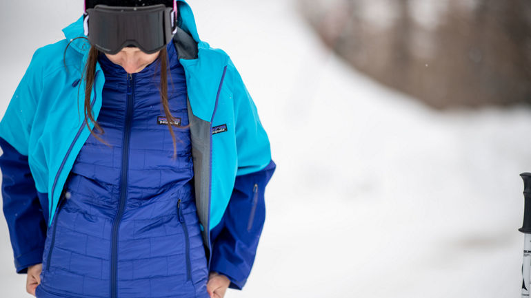 Female snowboarder putting on a jacket over a mid-layer from Patagonia