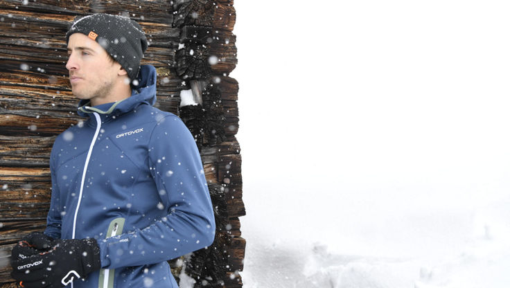 A male snowboarder outside wearing a blue zip hoodie from ortovox
