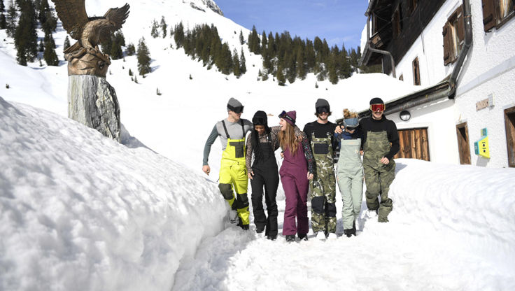 A group of snowboarders standing in snow in bib-pants