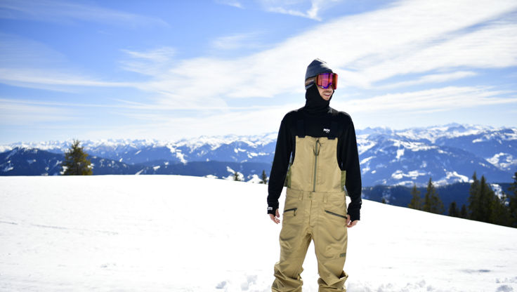 A snowboarder standing in snow in bib-pants