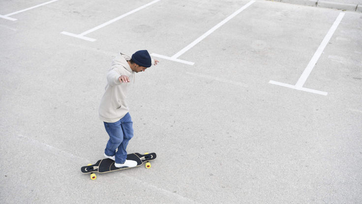 Young man riding his longboard