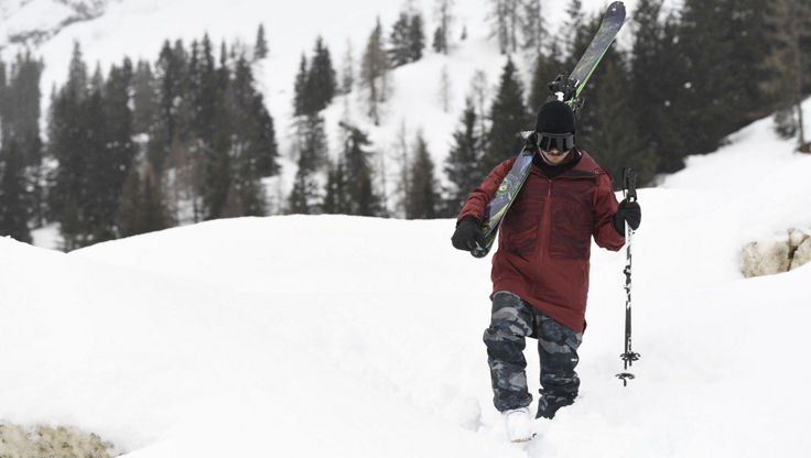 Snowboarder walking with longer cut jackets