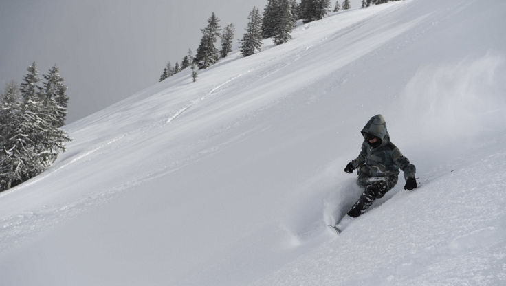 A skier enjoying a powder turn with a warm jacket