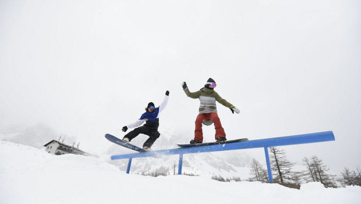 Two snowboarders sliding over an rail with medium insulation jackets
