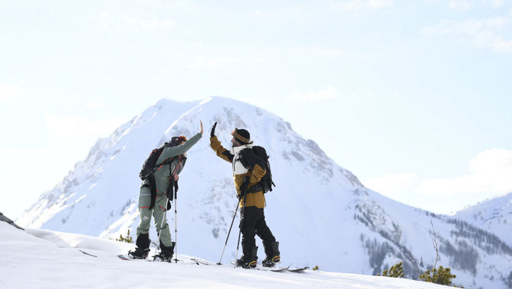 Two Splitboarders celebreate with a high five after making peak