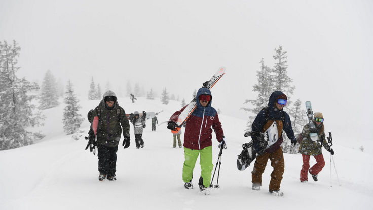 Four friends walking in deep snow with their skis and snowboards