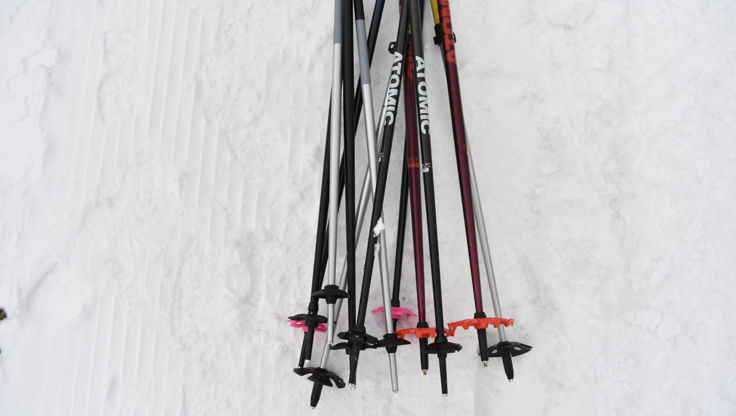 Splitboard poles of different materials lying in the snow