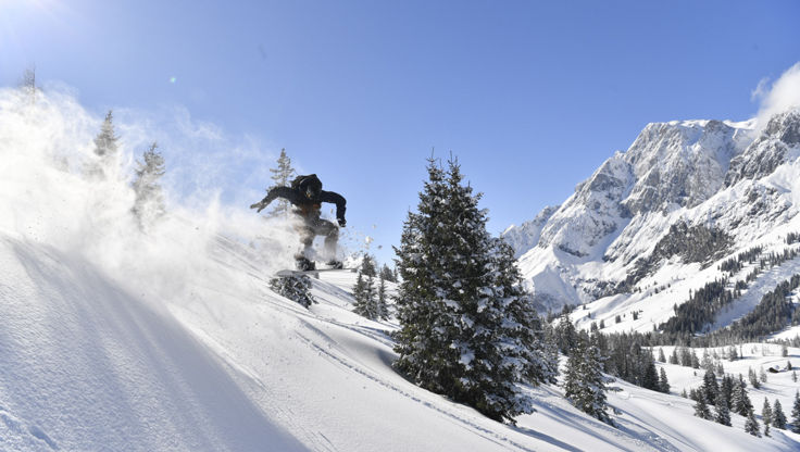 A snowboarder jumping in untouched fresh powder