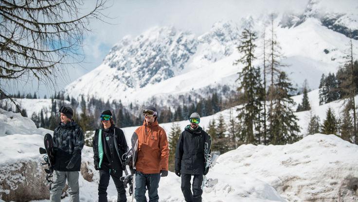 Intermediate snowboarders walking back from riding