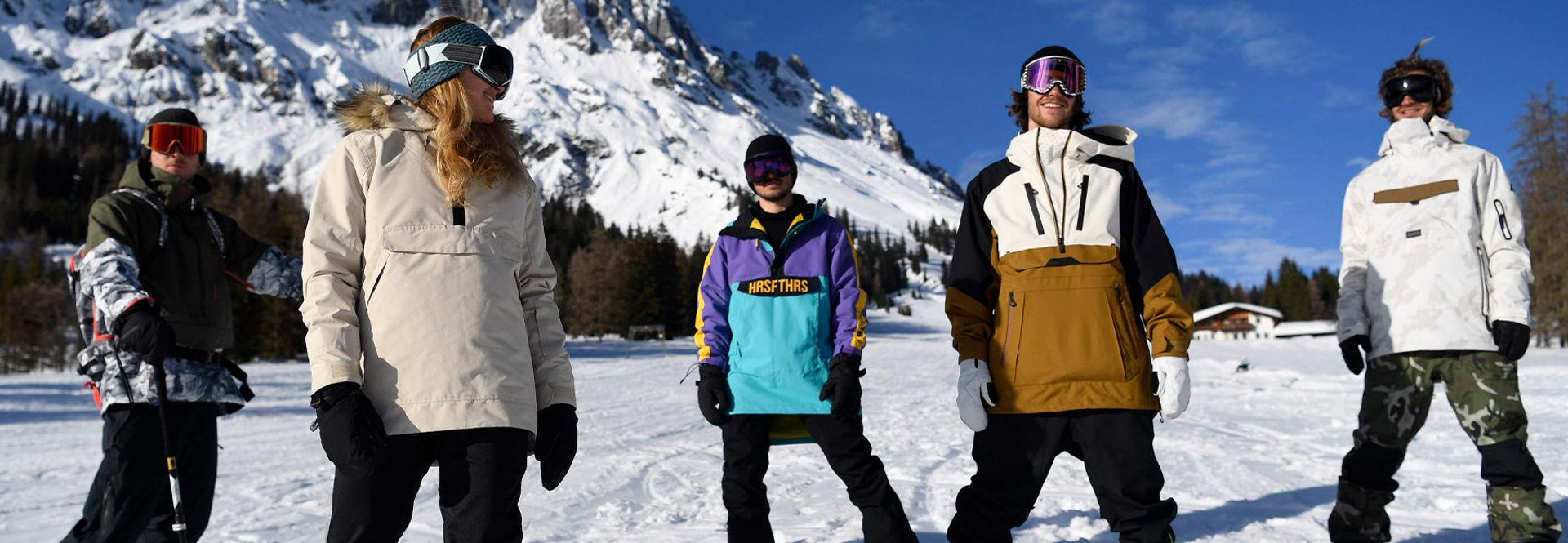 Eine Gruppe von Skiern und Snowboardern stehen draußen mit ihren Brettern und Snowwear