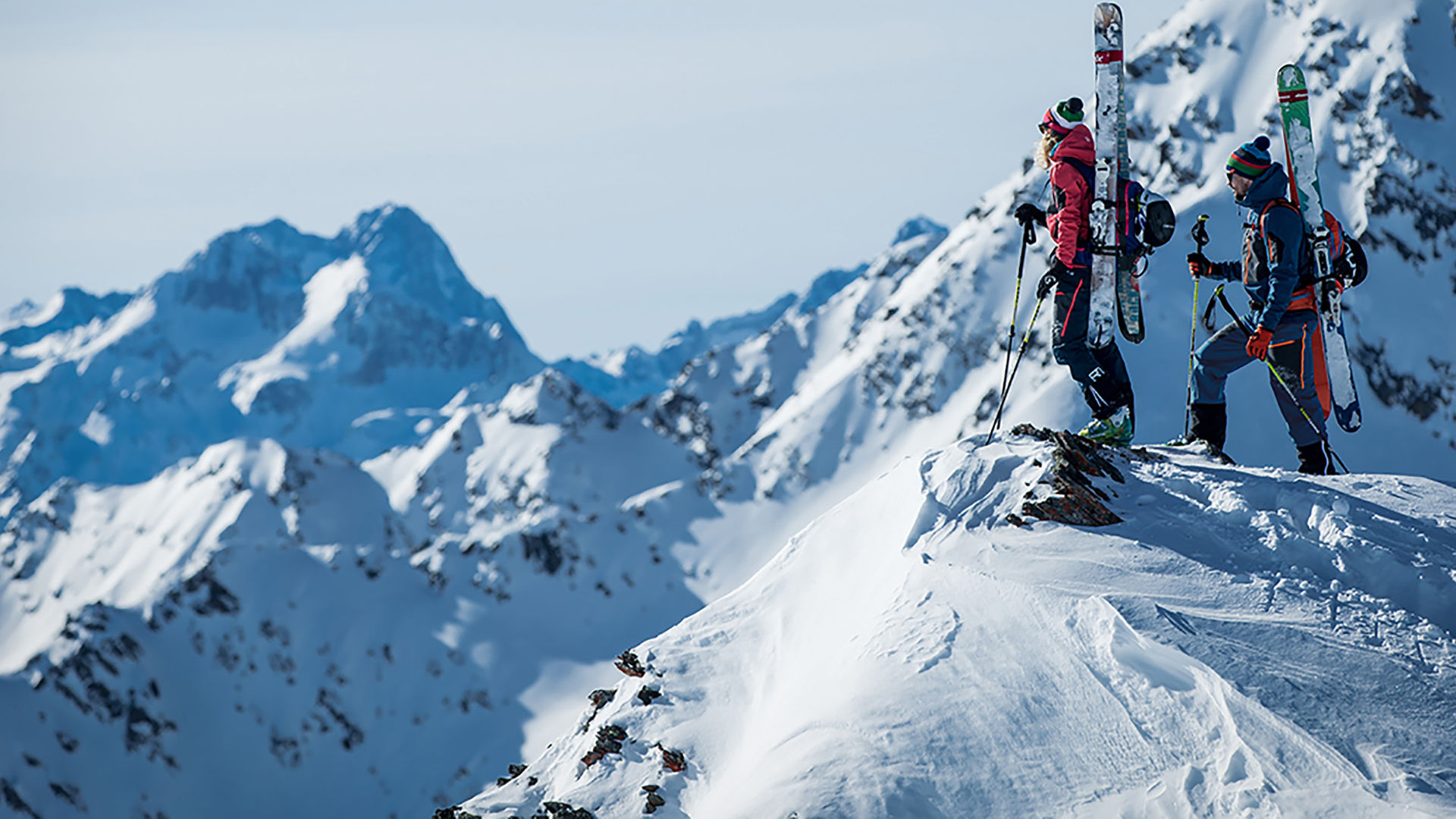Two freeride skiers standing on top of the mountain searching for the perfect line