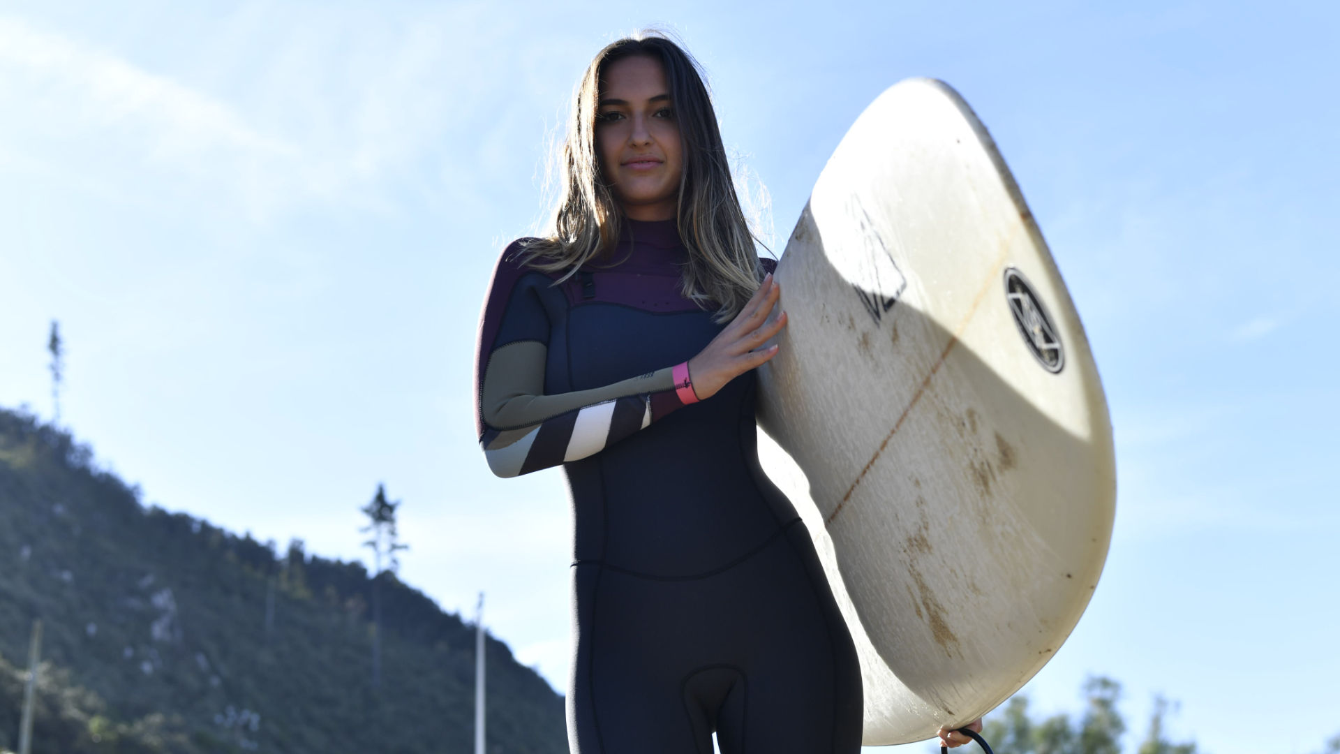 Surfer girl about to go in colder waters with a 3/2 wetsuit