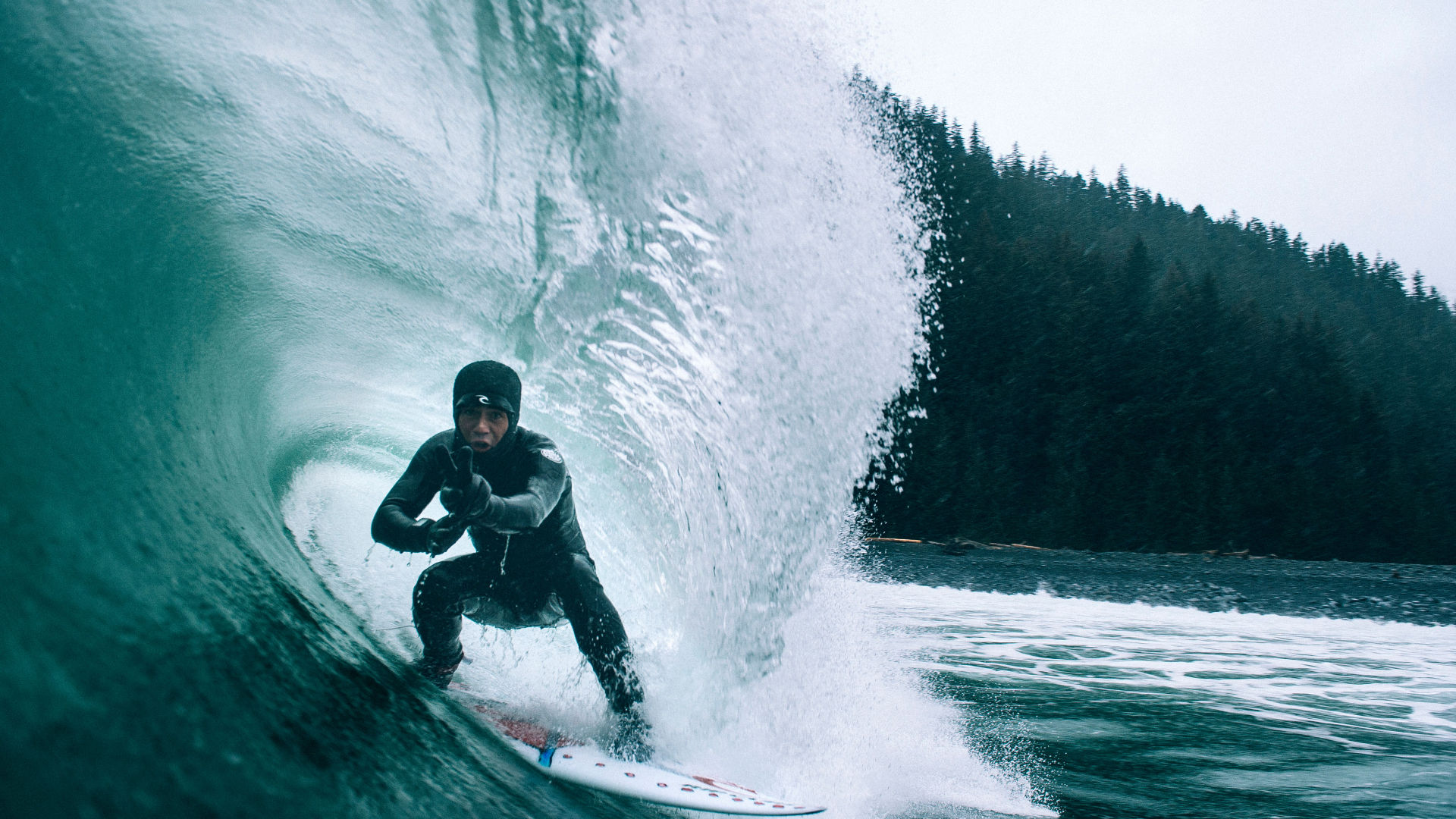 Surfer in Alaskan cold waters with booties and a hood