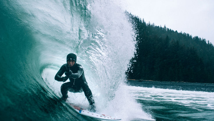 Surfer surfing in the cold waters of Alaska