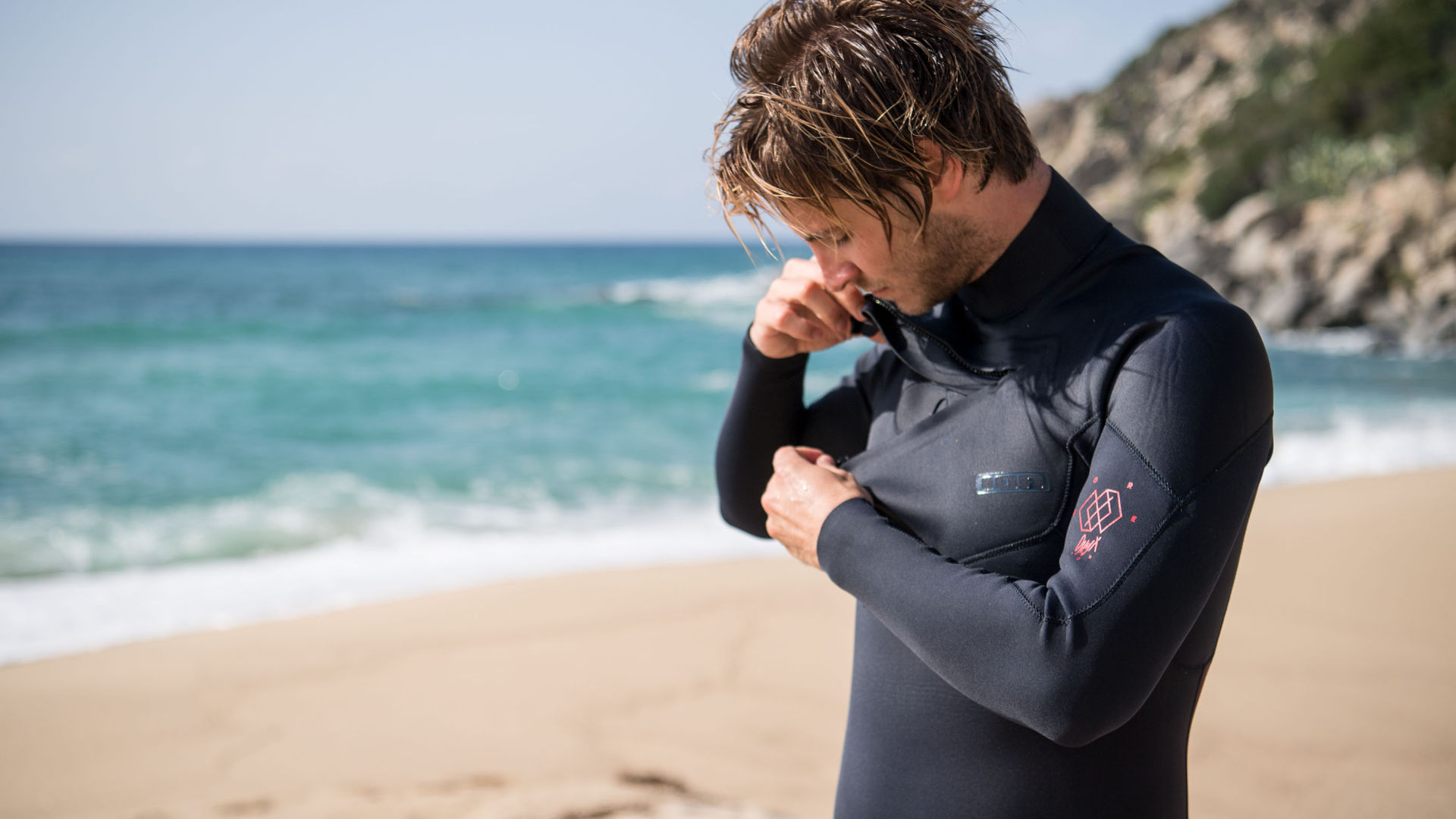 Surfer getting into his chest zip wetsuit