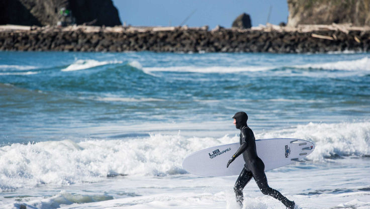 Sufer in a full wetsuit, hood, boots and gloves going for a surf