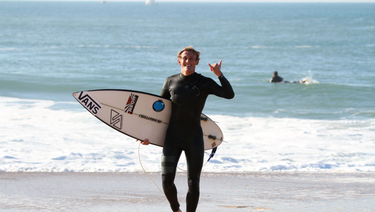 A happy surfer after a good session in a no zip wetsuit