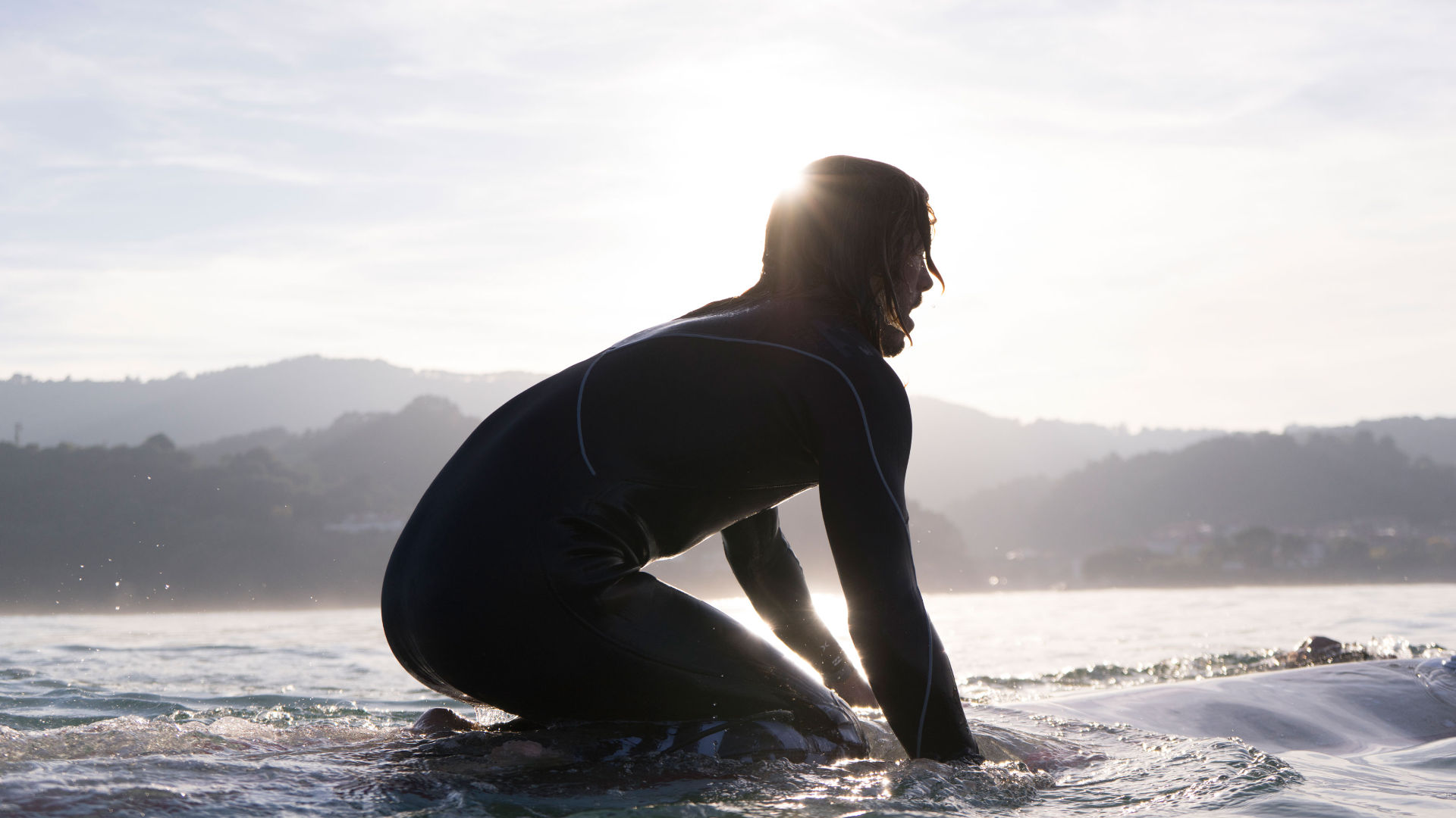 A man sitting on his surfboard in the sea wearing a wetsuit