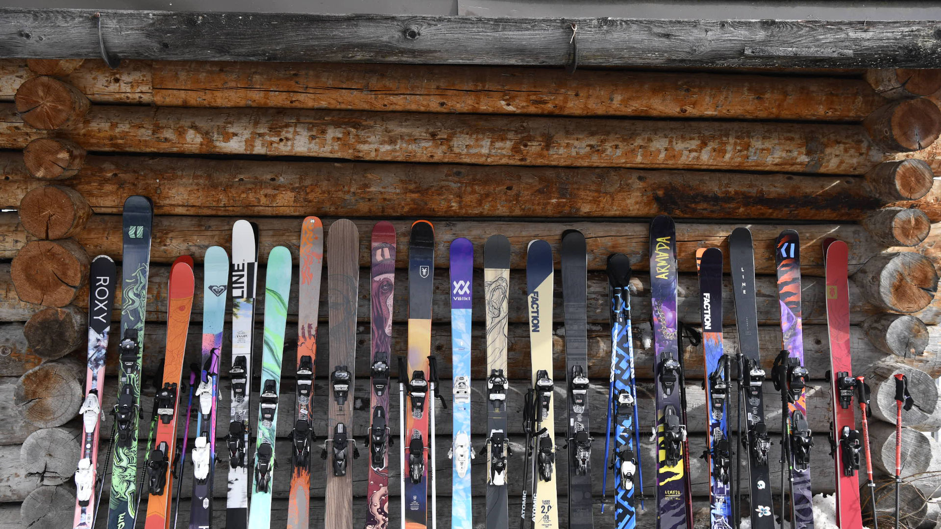 Variety of different skis against a wooden wall