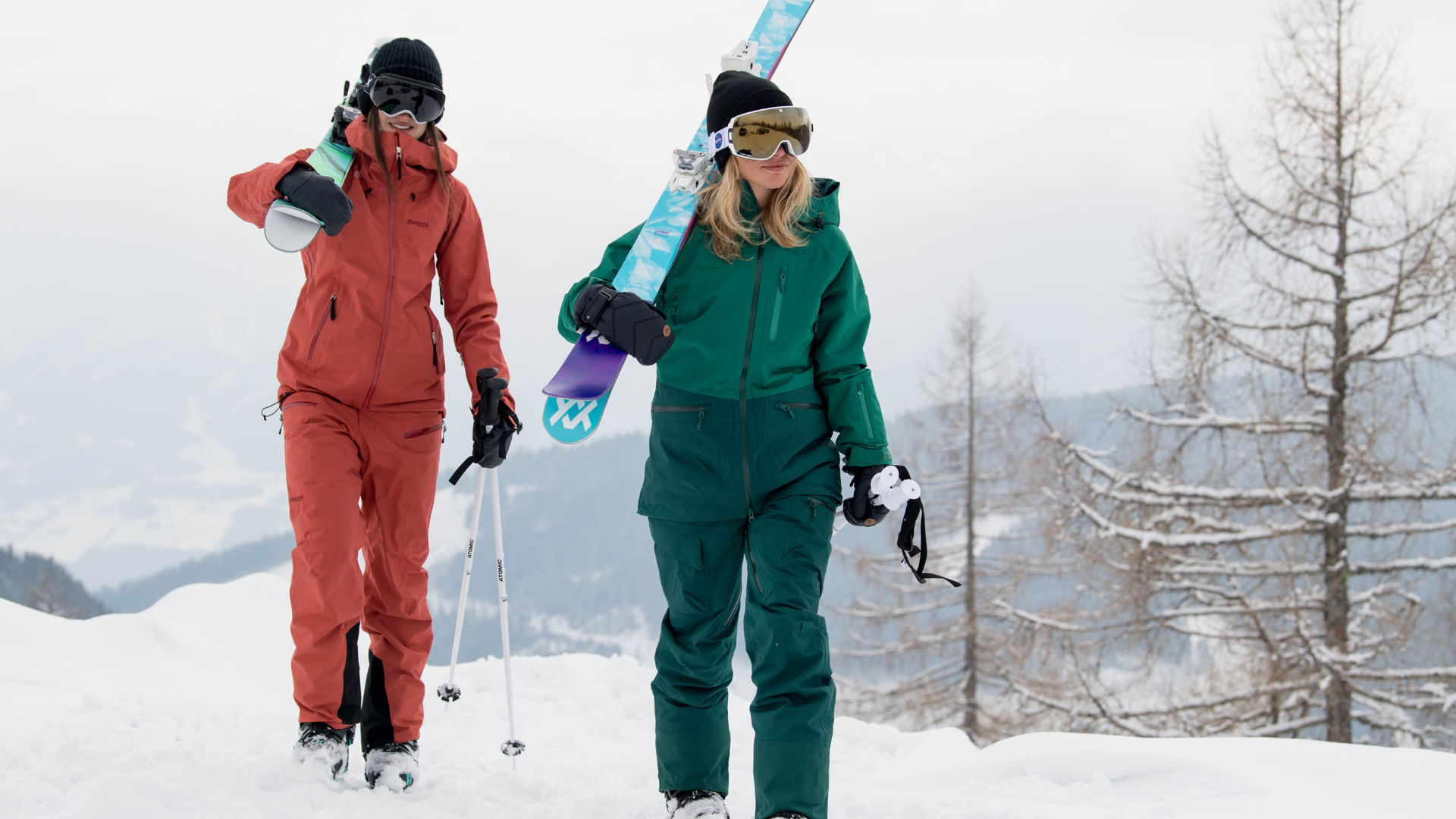 Two beginner skiers walking with skis over thier shoulders