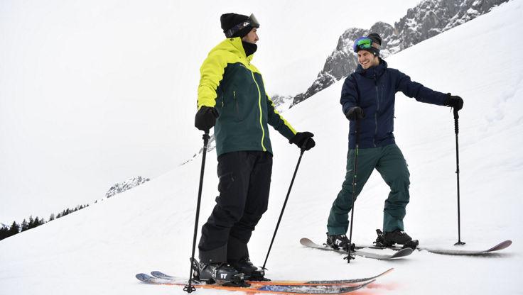 Two intermediate skiers on freeride skis