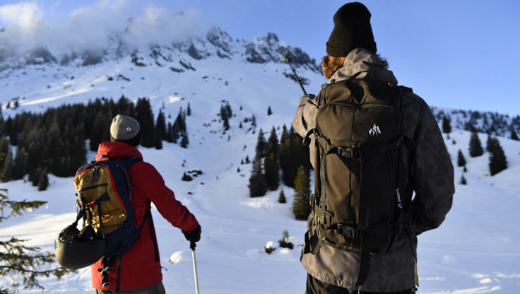 Zwei Skitourengeher, die mit ihren verstellbaren Stöcke auf einem Berg hinweisen.