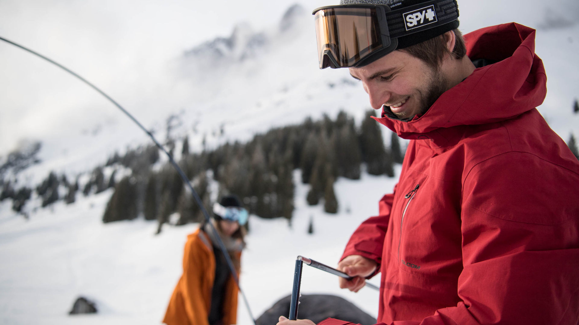 A male snowboarder wearing Medium Size Snowboard Goggles from SPY Optics