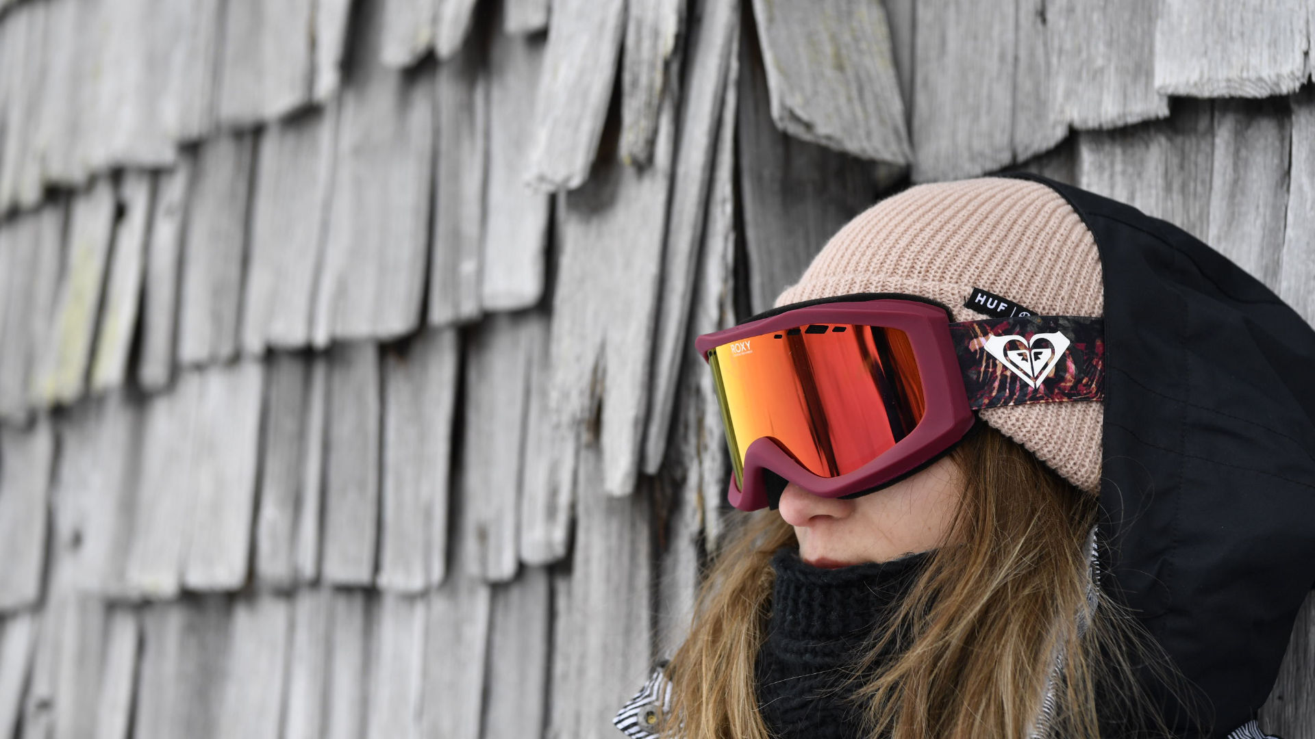 A girl wearing a small snowboard goggle