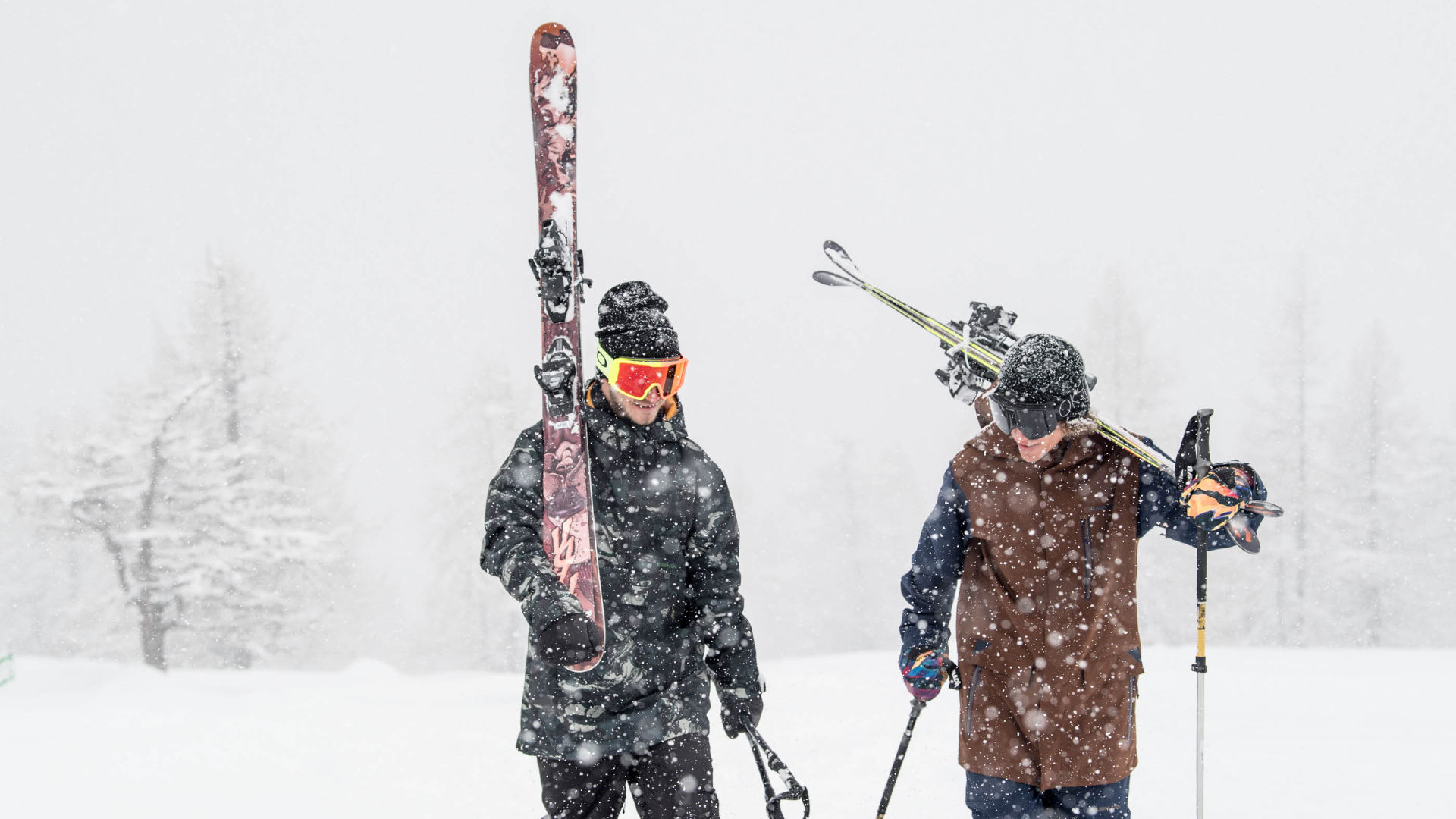 Two skiers hiking through heavy snow with anti-fog goggles