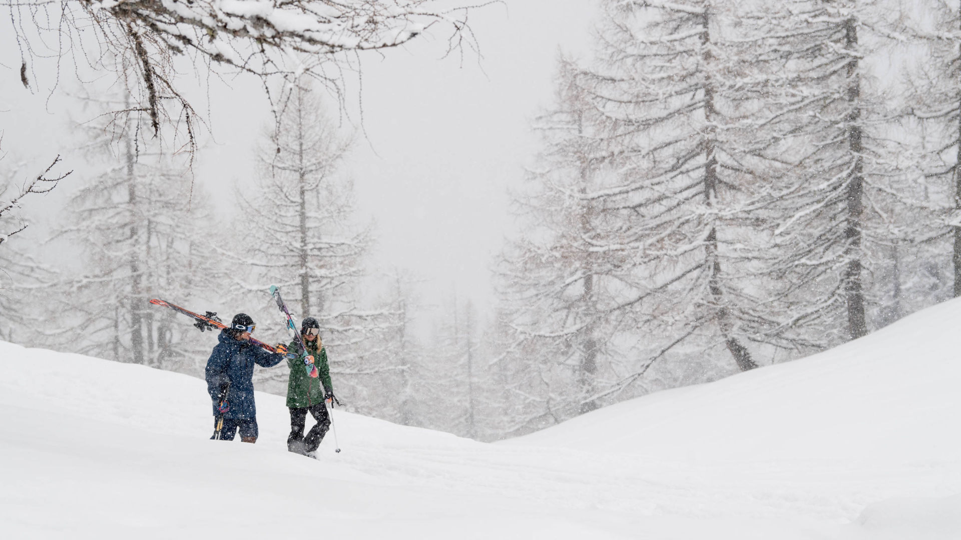 Two skiers walking in overcast and snowing conditions in the mountains